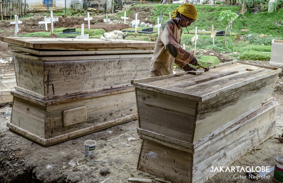 Suherman prepares coffins ordered to be donated for the coronavirus disease (COVID-19) victims in Pondok Kelapa public cemetery in East Jakarta. (JG Photo/Catur Nugroho)