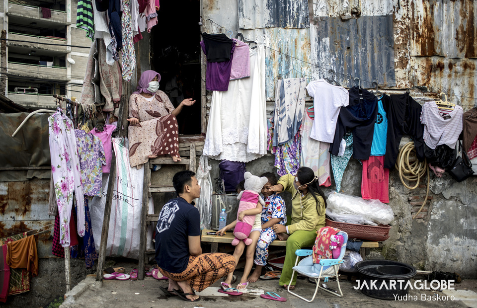 A family sunbathe together outside of their home in Petamburan, Central Jakarta on Friday (10/04). (JG Photo/Yudha Baskoro)