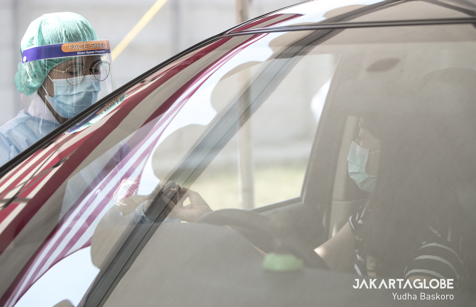 A health worker takes a blood sample through a car window to implementing physical distancing. (JG Photo/Yudha Baskoro)