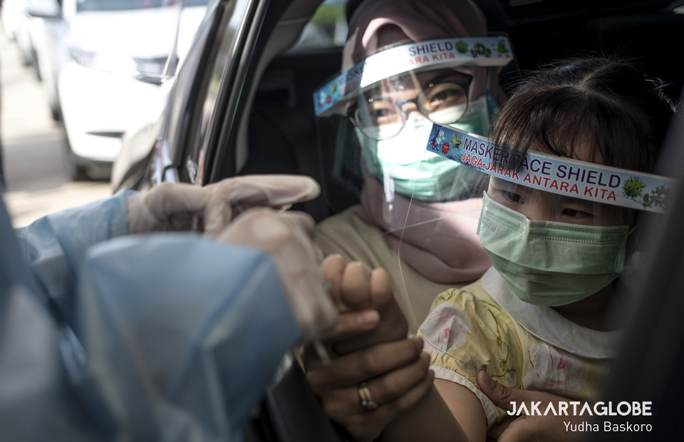 A health workers takes a blood sample from a child through a window car during rapid testing for coronavirus outside Lippo Mall Puri, West Jakarta on Saturday (18/04). (JG Photo/Yudha Baskoro)