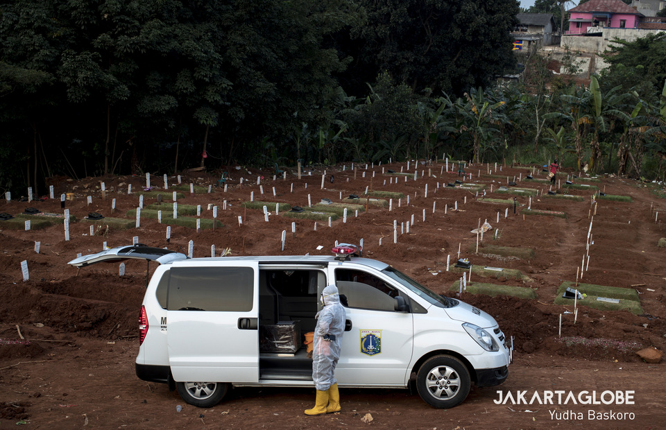 A funeral service worker gestures outside an ambulance car carrying covid-19 victims coffin at Pondok Ranggon public cemetery in East Jakarta on Wednesday (22/04). (JG Photo/Yudha Baskoro)