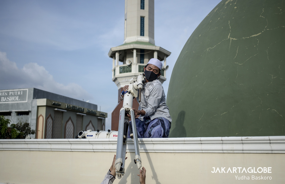 A boarding school student wearing protective masks help his friend to put the tripod on the roof of Al Musariin mosque. (JG Photo/Yudha Baskoro)