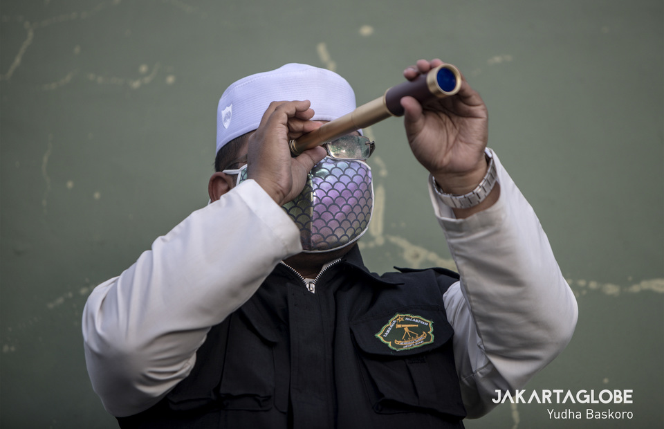 A muslim cleric wearing protective mask use a monoscope to observe the hilal on the rooftop of Al Mujariin mosque in West Jakarta. (JG Photo/Yudha Baskoro)