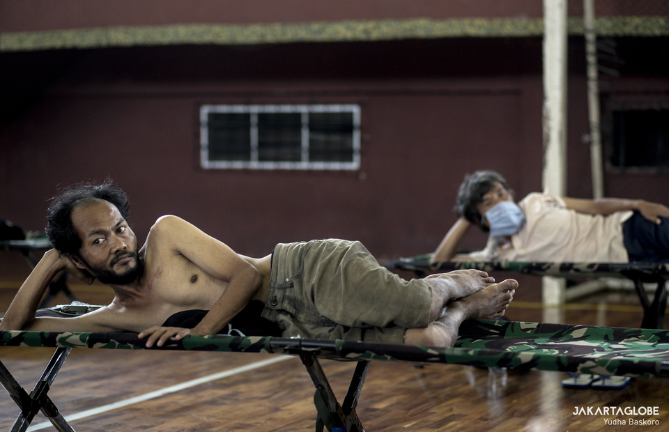 Two homeless man relax on a makeshift bed inside Ciracas sport hall on Friday (01/05). (JG Photo/Yudha Baskoro)