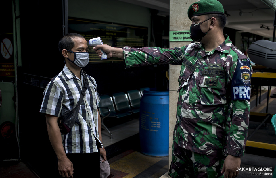 Indonesian army personnel check the body temperature to a resident. (JG Photo/Yudha Baskoro)