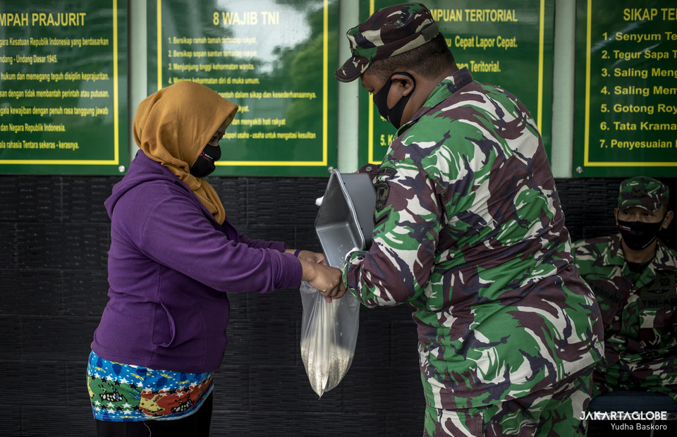 A woman receive a 1.5 kg of rice from rice ATM at Kodim 0503, West Jakarta on Monday (04/05). (JG Photo/Yudha Baskoro)