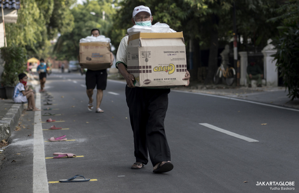 A man brings a box of foods and walks alongside a line of flip-flops. (JG Photo/Yudha Baskoro)