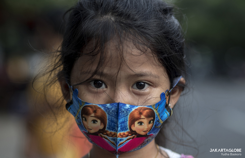 A child wearing face mask with picture of Disney character during free takjil distribution in Cempaka Putih Raya, Central Jakarta on Wednesday (13/05). (JG Photo/Yudha Baskoro)