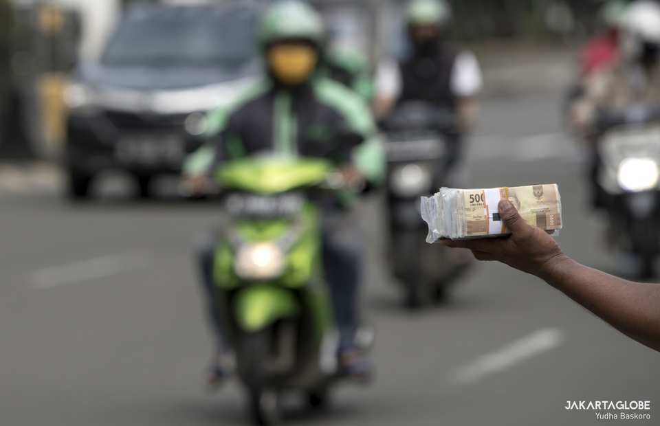 Street vendor offers new money to motocyclist in Jakartas Old Town area in North Jakarta on Thursday (21/05). (JG Photo/Yudha Baskoro)