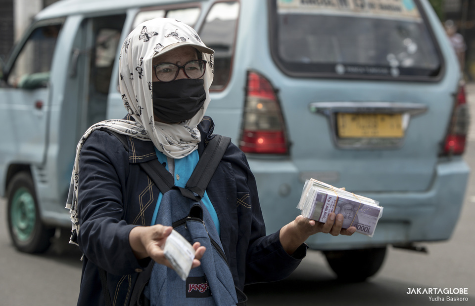 A woman wearing face mask sells fresh money on cash before Lebaran day. (JG Photo/Yudha Baskoro)