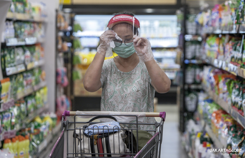 A woman wipes her sweat as she goes shopping at AEON supermarket on Tuesday (26/05). (JG Photo/Yudha Baskoro)