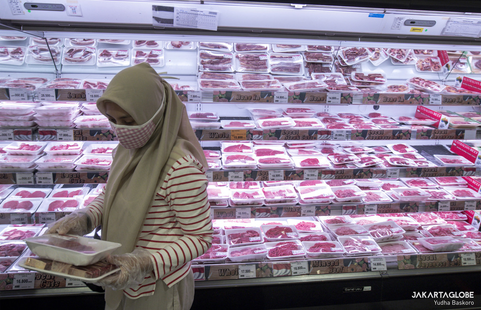 A woman wearing face mask buy raw meat in AEON supermarket on Tuesday (26/05). (JG Photo/Yudha Baskoro)