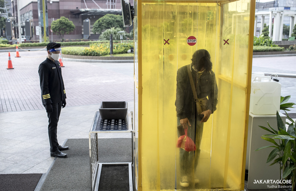 A man walks into a disinfection chamber in front of Senayan City mall in Central Jakarta on Tuesday (09/06). (JG Photo/Yudha Baskoro)