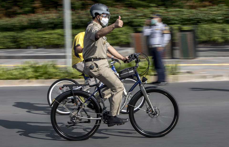 The Jakarta governor, Anies Baswedan gives a thumbs up while rides his bicycle in Central Jakarta on Tuesday (16/06). (JG Photo/Yudha Baskoro)