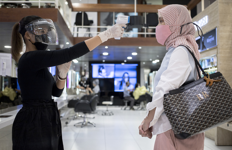 Salon employee checks a customers body temperature at Alfons Haircode salon inside Lotte Shopping Avenue in South Jakarta on Friday (19/06). (JG Photo/Yudha Baskoro)