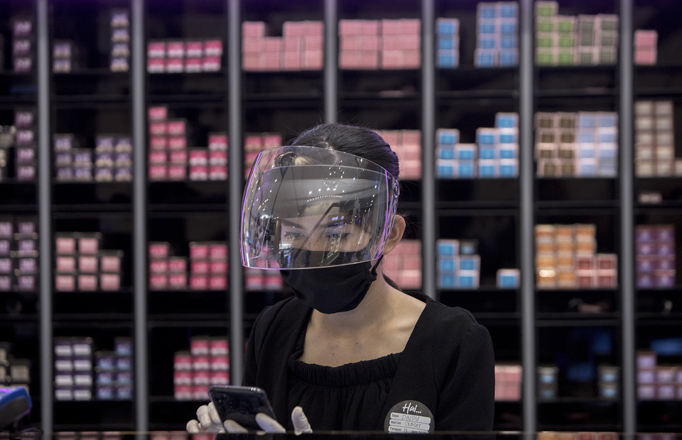 A salon employee accepts booking reservation through a mobile phone at Alfons Haircode salon inside Lotte Shopping Avenue in South Jakarta on Friday (19/06). (JG Photo/Yudha Baskoro)