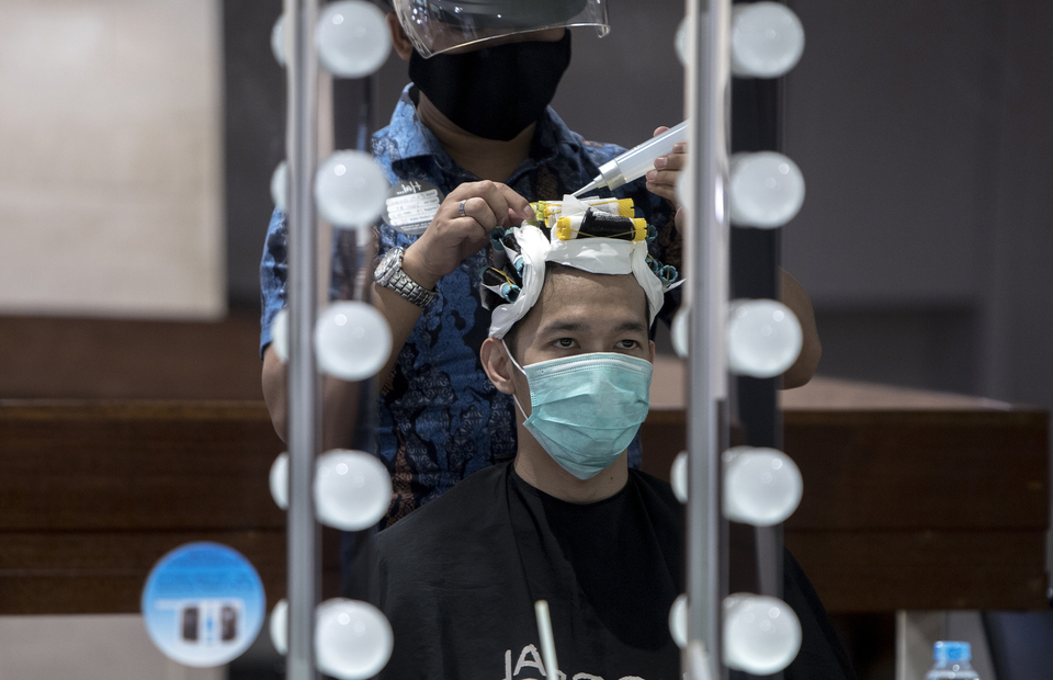 A man wearing mask as he cuts his hair at Alfons Haircode salon inside Lotte Shopping Avenue in South Jakarta on Friday (19/06). (JG Photo/Yudha Baskoro)