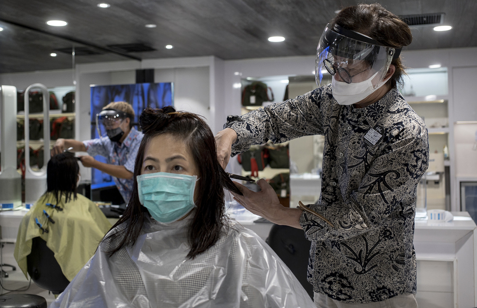 A hairdresser wearing face shield and mask cuts customers hair at Alfons Haircode salon inside Lotte Shopping Avenue in South Jakarta on Friday (19/06). (JG Photo/Yudha Baskoro)