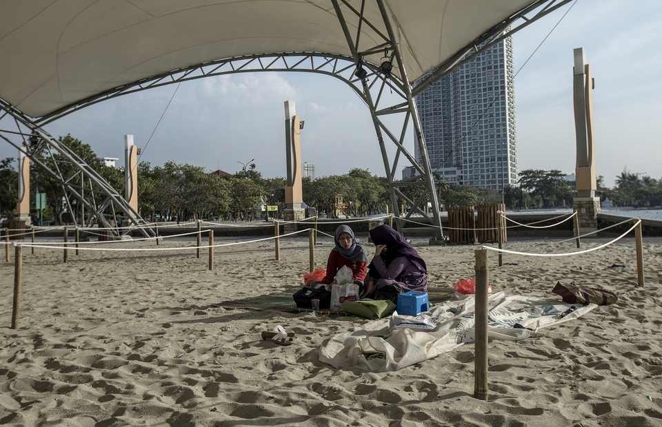 Visitors sit on a beach with physical distancing guidelines at Ancol Beach in North Jakarta on Saturday (20/06). (JG Photo/Yudha Baskoro)