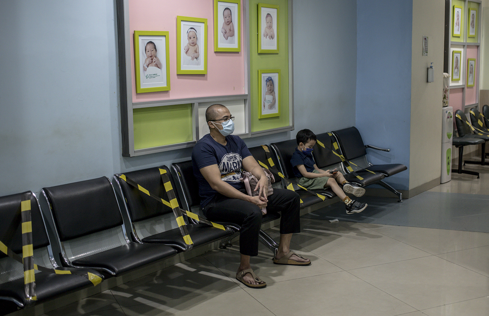 A father and his son sit in a waiting room at Tambak Children