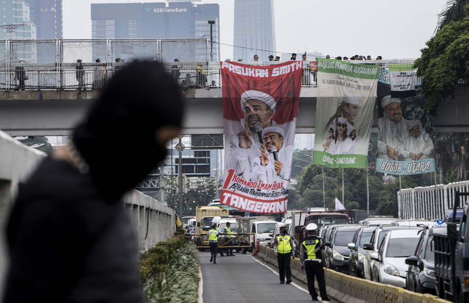 Giant banners with picture of Habib Rizieq were seen on a pedestrian bridge during protest in front of national legislative complex in Senayan, Central Jakarta, on Wednesday (24/06). (JG Photo/Yudha Baskoro)