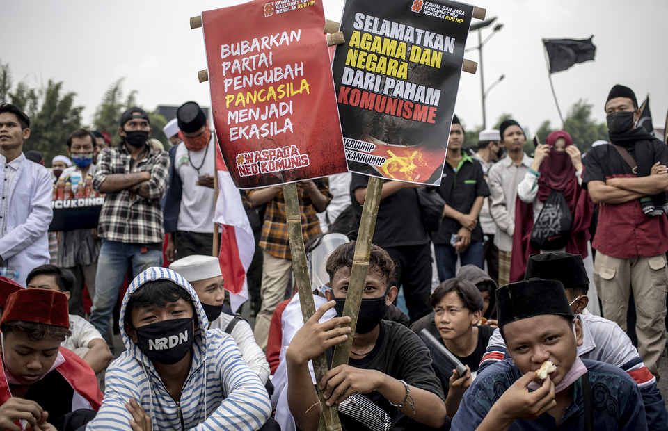 Protesters carry some posters with anti-communism jargon during protest in front of national legislative complex in Senayan, Central Jakarta, on Wednesday (24/06). (JG Photo/Yudha Baskoro)