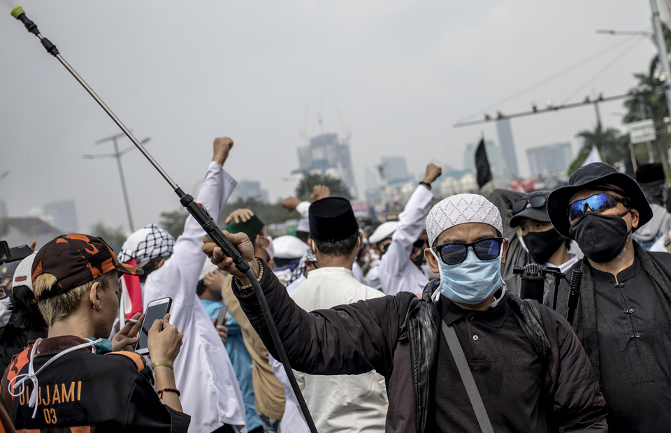 Protester sprays disinfectant in the middle of the crowd during protest in front of national legislative complex in Senayan, Central Jakarta, on Wednesday (24/06). (JG Photo/Yudha Baskoro)