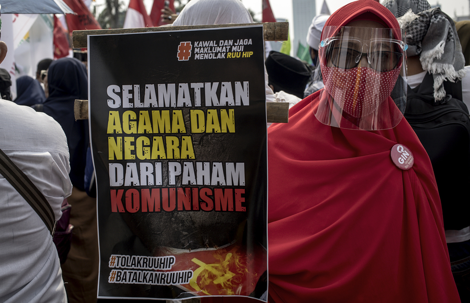 A woman wearing face shield and mask, brings a poster with anti-communism jargon during protest in front of national legislative complex in Senayan, Central Jakarta, on Wednesday (24/06). (JG Photo/Yudha Baskoro)