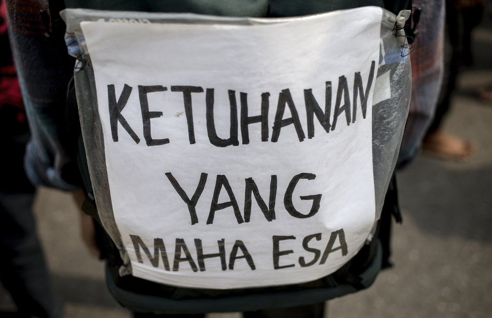 A protester puts a poster on his bag written the first sila from Pancalisa Ketuhanan Yang Maha Esa during protest in front of national legislative complex in Senayan, Central Jakarta, on Wednesday (24/06). (JG Photo/Yudha Baskoro)