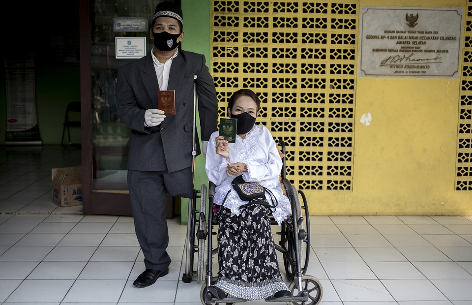 Anwar and Warni wearing mask, show their wedding book during their wedding ceremony in Office of Religion Affairs in Cilandak, South Jakarta on Tuesday (01/07). (JG Photo/Yudha Baskoro)