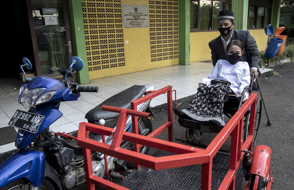 Anwar helps his wife to get into their special modification bike in Office of Religion Affairs in Cilandak, South Jakarta on Tuesday (01/07). (JG Photo/Yudha Baskoro)
