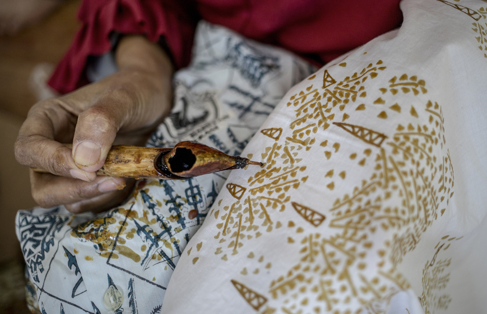 A batik artisan paints a coconut flowers motif on a fabric at Rusun Marunda, North Jakarta on Wednesday (01/07). (JG Photo/Yudha Baskoro)