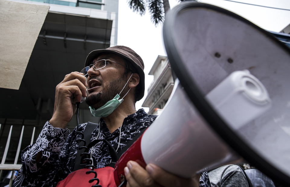 A refugee speaks with a microphone during protest in front of UNHCR office building in Kebon Sirih, Central Jakarta on Monday (13/07). (JG Photo/Yudha Baskoro)