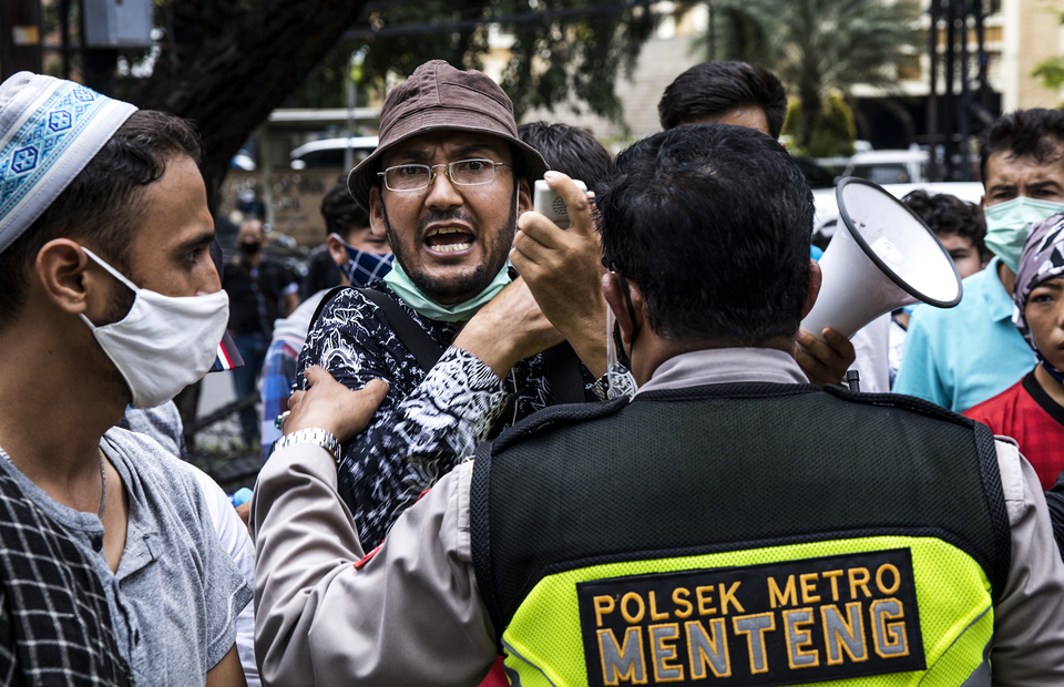 A refugee tries to enter the UNHCR office building during protest in front of UNHCR office building in Kebon Sirih, Central Jakarta on Monday (13/07). (JG Photo/Yudha Baskoro)