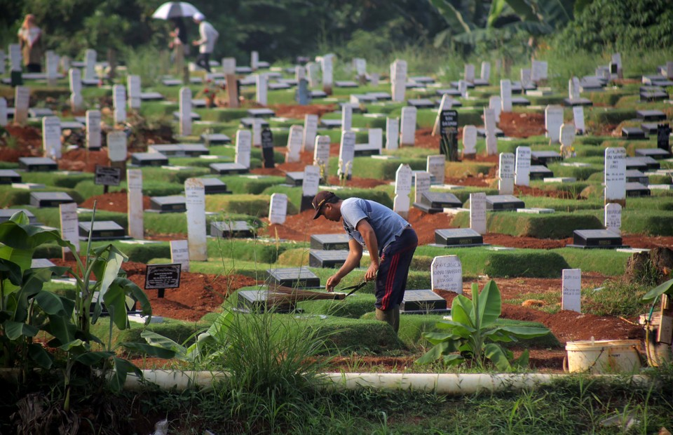 A man cleans a graveyard at the Pondok Rangon public cemetery in East Jakarta on July 19, 2020. The cemetery is intended for Covid-19 victims. (B1 Photo/Joanito de Saojoao)