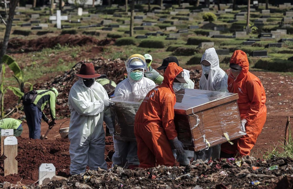 Medical workers carry the coffin of a deceased Covid-19 patient at Pondok Rangon public cemetery in East Jakarta on July 7, 2020. (B1 Photo/Joanito de Saojoao)