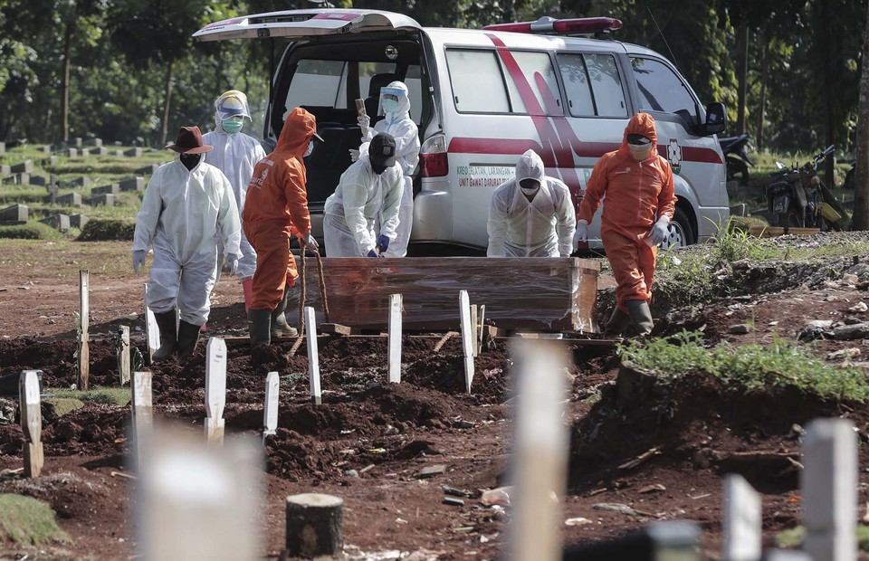 Medical workers prepare the burial of a deceased Covid-19 patient at Pondok Rangon public cemetery in East Jakarta on July 7, 2020. (B1 Photo/Joanito de Saojoao)