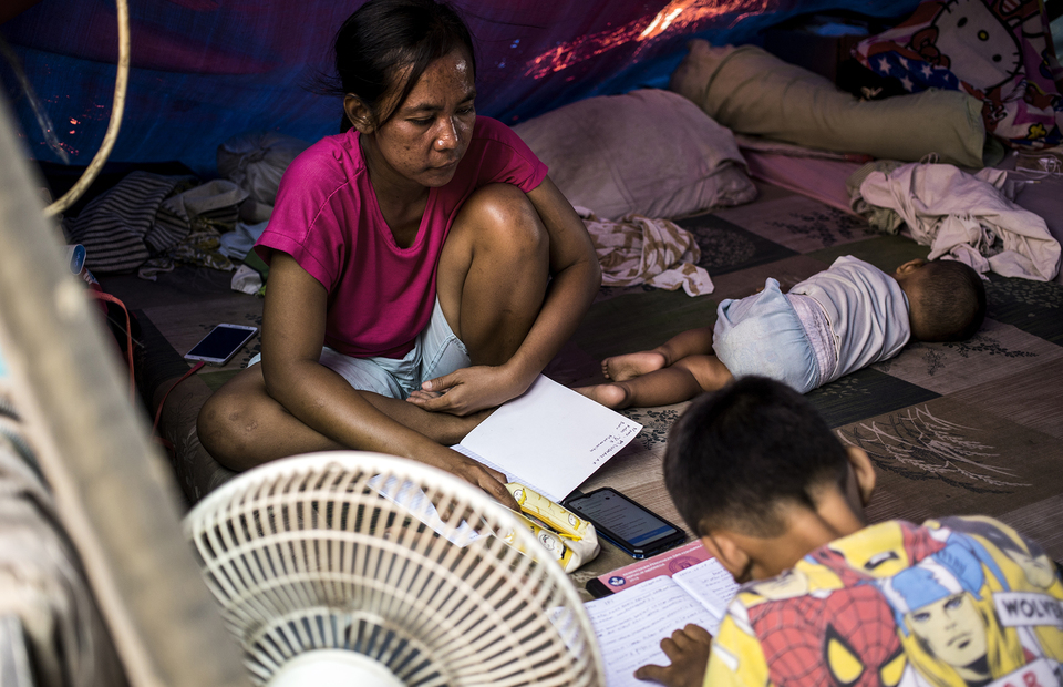 A mother accompanies her son as he studies online inside makeshift tent at Kampung Bandan, North Jakarta on Monday (20/07). (JG Photo/Yudha Baskoro)