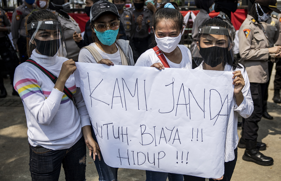 Protesters carry a poster that reads widow need money for living during protest in front of Jakarta City Hall in Central Jakarta on Tuesday (21/07). (JG Photo/Yudha Baskoro)