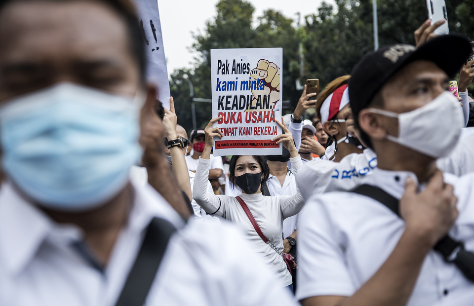 Protester wearing mask carries a poster during protest in front of Jakarta City Hall in Central Jakarta on Tuesday (21/07). (JG Photo/Yudha Baskoro)