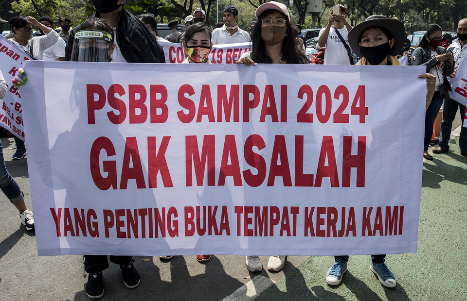 Protesters bring a poster that reads Large Scale Social Restrictions until 2024 is not problem if you reopen the nightclub during protest in front of Jakarta City Hall in Central Jakarta on Tuesday (21/07). (JG Photo/Yudha Baskoro)