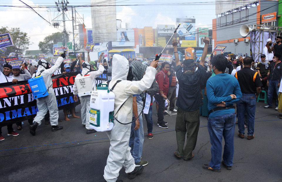 Supporters of impeachment motion against Jember District Head Faida are sprayed with disinfectant by medical workers at the district legislative compound in Jember, East Java, on July 22, 2020. (Antara Photo/Seno)