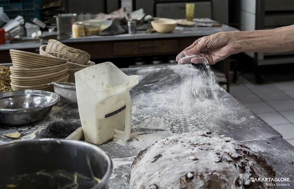 Heru pours flour to a dough inside Maison Weiner bakery in Senen, Central Jakarta on Friday (24/07). (JG Photo/Yudha Baskoro)