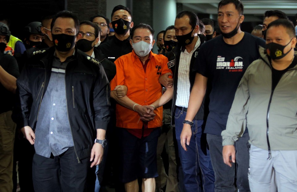 Graft fugitive Djoko Tjandra, center, is escorted by police officers upon arrival at the Halim Perdanakusumah Airport in East Jakarta after a flight from Kuala Lumpur  on July 30, 2020. (Beritasatu Photo/Joanito De Saojoao)