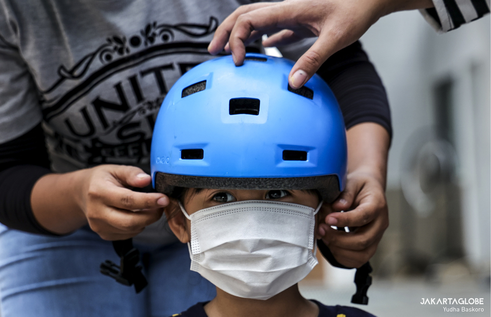 Parents help a child to wear a helmet during training at Duren Tiga, South Jakarta on Wednesday (05/08). (JG Photo/Yudha Baskoro)