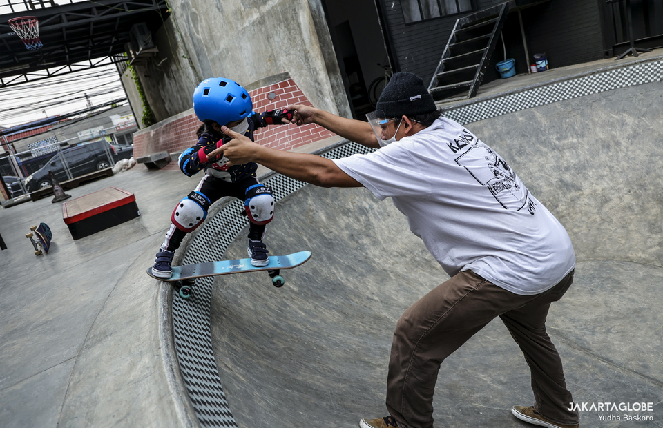 A young skater practices a new trick with her coach during training at Duren Tiga, South Jakarta on Wednesday (05/08). (JG Photo/Yudha Baskoro)