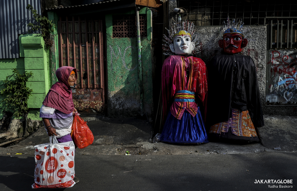 An old lady walks in front of ondel-ondel at Kramat Pulo, Central Jakarta on Friday (07/08). (JG Photo/Yudha Baskoro)