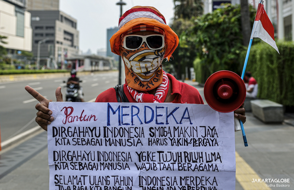 Die hard fans of Persija Jakarta holds placard during moment of silence to commemorate Indonesian declaration of independence in Hotel Indonesia roundabout at Central Jakarta on Monday (17/08). (JG Photo/Yudha Baskoro)