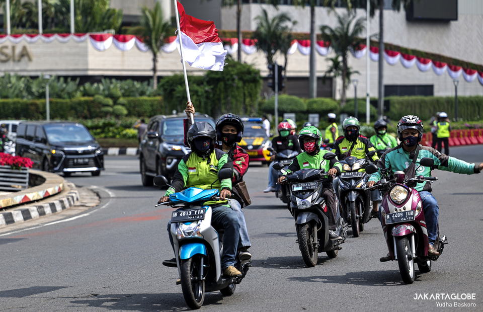 Online taxi drivers carry Indonesian flag, as they march to celebrate Indonesian independence day in Hotel Indonesia roundabout at Central Jakarta on Monday (17/08). (JG Photo/Yudha Baskoro)