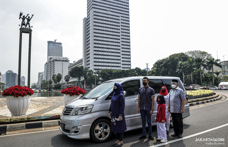 A family stand outside their car to pay tribute during moment of silence in Hotel Indonesia roundabout at Central Jakarta on Monday (17/08). (JG Photo/Yudha Baskoro)